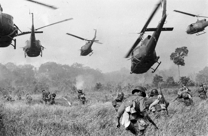Hovering U.S. Army helicopters pour machine gun fire into a tree line to cover the advance of South Vietnamese ground troops in an attack on a Viet Cong camp 18 miles north of Tay Ninh, northwest of Saigon near the Cambodian border, in Vietnam on March 1965. (AP Photo/Horst Faas)