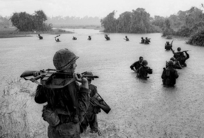 Paratroopers of the U.S. 2nd Battalion, 173rd Airborne Brigade hold their automatic weapons above water as they cross a river in the rain during a search for Viet Cong positions in the jungle area of Ben Cat, South Vietnam on Sept. 25, 1965. (AP Photo/Henri Huet)