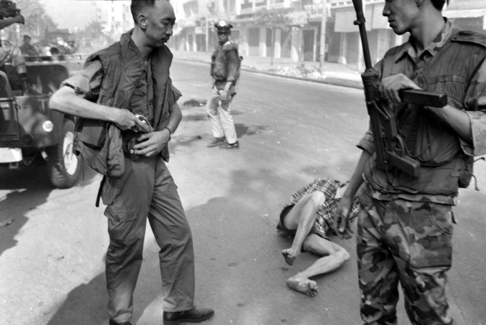 (3 of 3) South Vietnamese General Nguyen Ngoc Loan holsters his gun after executing suspected Viet Cong officer Nguyen Van Lem whose body lies on a Saigon street Feb. 1, 1968, early in the Tet Offensive. (AP Photo/Eddie Adams)