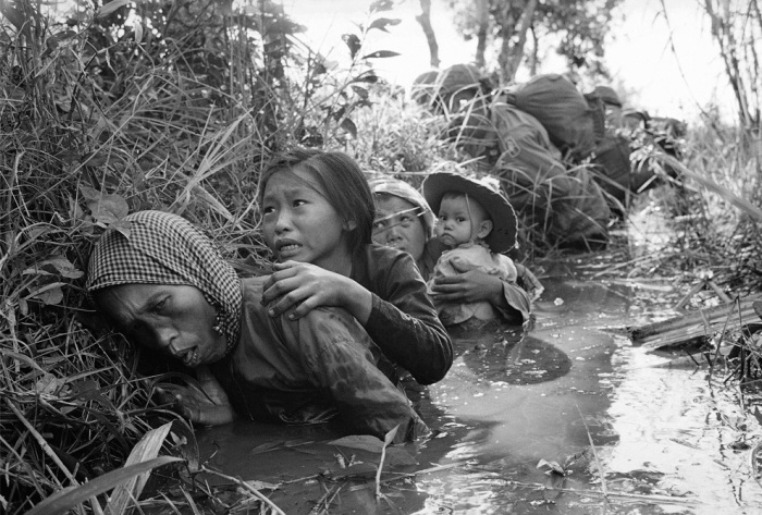 Women and children crouch in a muddy canal as they take cover from intense Viet Cong fire at Bao Trai, about 20 miles west of Saigon, Vietnam on Jan. 1, 1966. (AP Photo/Horst Faas)
