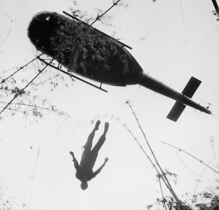 The body of an American paratrooper killed in action in the jungle near the Cambodian border is raised up to an evacuation helicopter in War Zone C, Vietnam in 1966. (AP Photo/Henri Huet)