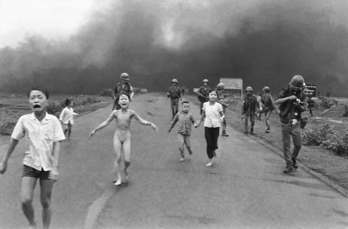 South Vietnamese forces follow after terrified children, including 9-year-old Kim Phuc (center left), as they run down Route 1 near Trang Bang after an aerial napalm attack on suspected Viet Cong hiding places, June 8, 1972. A South Vietnamese plane accidentally dropped its flaming napalm on South Vietnamese troops and civilians. The terrified girl had ripped off her burning clothes while fleeing. The children from left to right are: Phan Thanh Tam, younger brother of Kim Phuc, who lost an eye, Phan Thanh Phouc, youngest brother of Kim Phuc, Kim Phuc, and Kim's cousins Ho Van Bon, and Ho Thi Ting. Behind them are soldiers of the Vietnam Army 25th Division.