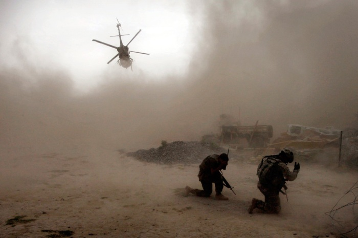 Soldiers with the U.S. Army's 1-320 Field Artillery Regiment, 101st Airborne Division shield themselves from the dust as a Medevac helicopter takes off outside Combat Outpost Nolen in the Arghandab Valley north of Kandahar July 30, 2010. One soldier lost his leg and another was hit by shrapnel after an Improvised Explosive Device (IED) blew up during a patrol near the base. (REUTERS/Bob Strong)