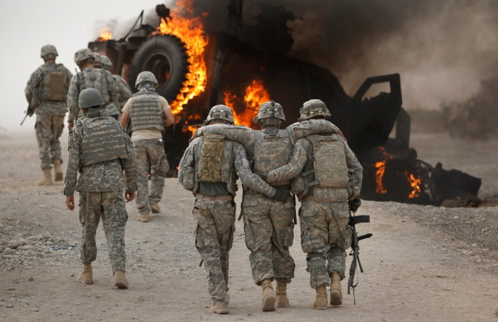 A soldier with an injured ankle from the US Army's 1-320 Field Artillery Regiment, 101st Airborne Division is assisted past his burning M-ATV armored vehicle after it struck an Improvised Explosive Device (IED) on a road near Combat Outpost Nolen in the Arghandab Valley in this picture taken July 23, 2010. None of the four soldiers in the vehicle were seriously injured in the explosion. (REUTERS/Bob Strong)