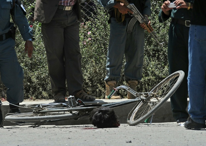 Afghan security personnel stand near the severed head of a suicide bomber at the site of a suicide attack in Kabul on July 18, 2010. A suicide bomber on a bicycle detonated explosives in central Kabul July 18, injuring six people, two days before a key international conference in the capital, a government official told AFP. (MASSOUD HOSSAINI/AFP/Getty Images)