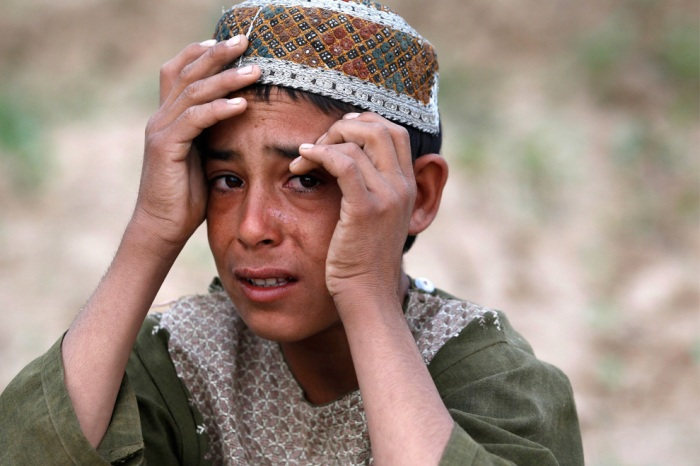 A boy weeps for a man who US Army soldiers said fired on them with an AK-47 was shot and killed near the village of Samir Kalacheh in Arghandab Valley north of Kandahar July 28, 2010. (REUTERS/Bob Strong)