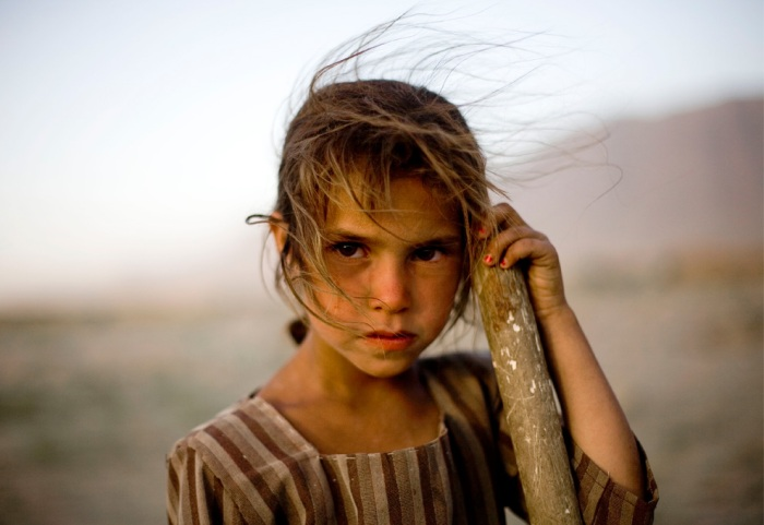 An Afghan girl who fixes potholes in a road between Kabul and Bagram and depends on tips from passing motorists, waits for vehicles in Afghanistan, Tuesday, July 6, 2010. (AP Photo/Dusan Vranic)