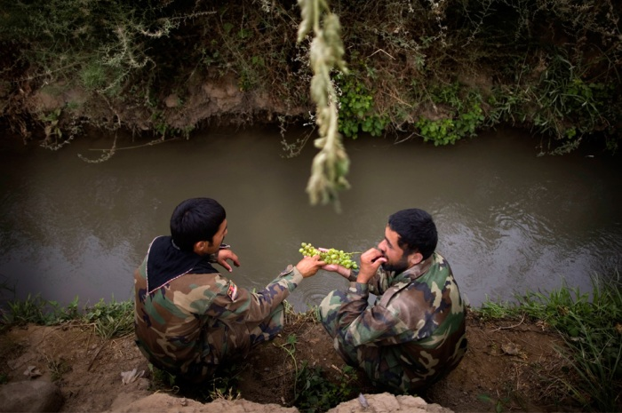 Afghan army soldiers share grapes beside a small canal after arriving to reinforce U.S. troops at Combat Outpost Nolen, in Arghandab Valley, in Kandahar, Afghanistan, Thursday, July 22, 2010. (AP Photo/Rodrigo Abd)