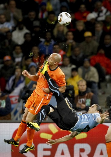Sports: 1st prize singles. Mike Hutchings, South Africa, Reuters. Netherlands Demy de Zeeuw is kicked in the face by Uruguay's Martin. Cáceres during World Cup semi-final, Cape Town, 6 July